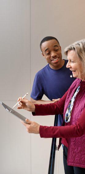 Retuschen Apple retail, Frau und Mann im Aufzug mit iPad