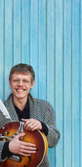 der Musiker Jesper Munk mit Gitarre vor einer blauen Holzwand